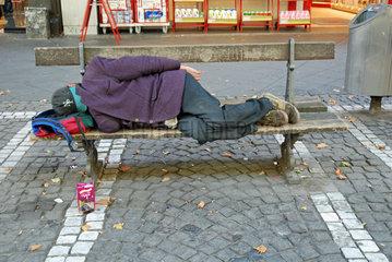 Obdachloser auf einer Bank vor einem Supermarkt