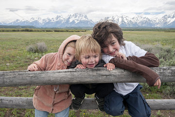 Children leaning against fence in Grand Teton National Park  Wyoming  USA