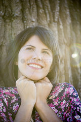 Woman leaning against tree  smiling  portrait