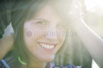 Woman smiling cheerfully outdoors  portrait