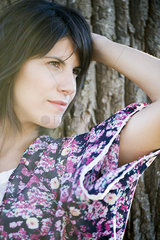 Woman leaning against tree trunk  looking away in thought