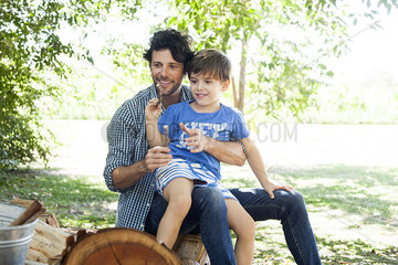 Little boy with father tossing sticks into bucket