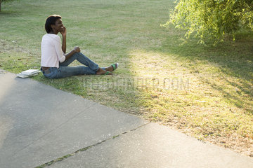 Young woman relaxing in park using cell phone