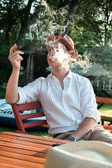 Mann raucht Zigarre im Freien