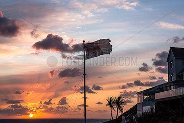 Zerrissene britische Nationalflagge nahe einem Hotel in der Abendsonne