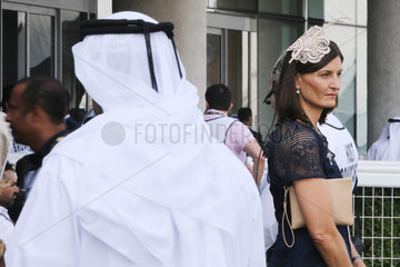 Dubai  Fashion  Lady with hat and man in traditional clothes at the racecourse