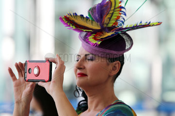 Dubai  Fashion  Lady with hat at the racecourse takes a picture with her mobilephone