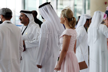 Dubai  Elegant dressed woman and men in traditional clothes at the racecourse