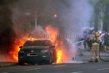 Berlin  Deutschland  Feuerwehrmann loescht ein brennendes Auto