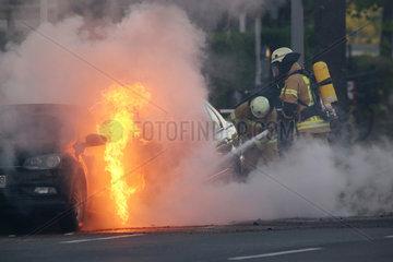 Berlin  Deutschland  Feuerwehrmaenner loeschen ein brennendes Auto