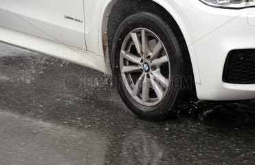 Teltow  Deutschland  Autoreifen bei der Fahrt auf nassem Asphalt