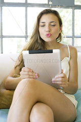 Woman video chatting using digital tablet