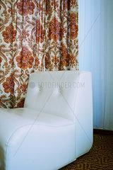 weisser Sessel und Mustervorhang