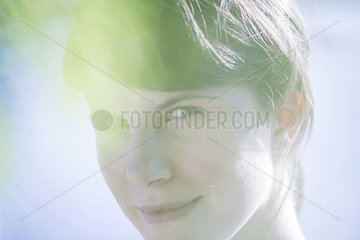 Woman smiling through foliage  portrait