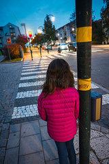 Kleines Maedchen wartet am Zebrastreifen auf gruenes Licht