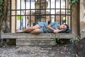 Junge Frau schlaeft auf einer Steinbank