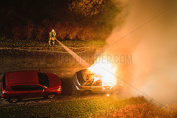 Feuerwehrmann loescht einen Pkw