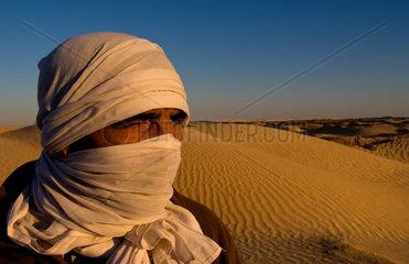 Graphic portrait of Bedouin man in Sahara Desert with sand in Douz Tunisia Africa
