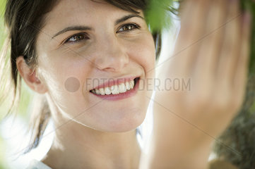Woman touching tree  smiling  portrait