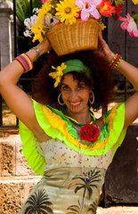 Portrait of smiling woman with flower basket in downtown Havana Cuba