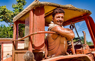 Man smiling in tractor cab after work in small village of Australia Cuba farm country