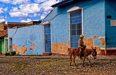 Old man with his donkey for rides on streets of old village of Trinidad Cuba