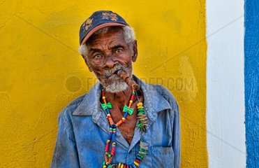 Colorful local man on yellow wall in colorful Trinidad Cuba Colonial city