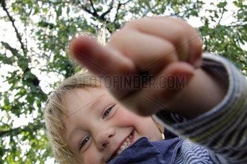 kleiner Junge  3 Jahre alt  schaut ins Objektiv der Kamera und beruehrt die Linse mit dem Finger (model released)