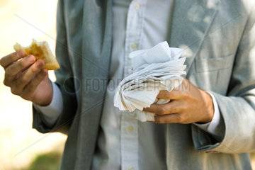 Person holding half eaten pastry in one hand and disposable cup and paper napkins in other hand