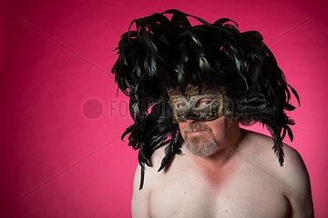 Mann mit nacktem Oberkoerper traegt Federn auf dem Kopf und eine Maske