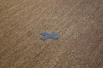 Silbernes X aus Klebeband auf einen Teppich geklebt