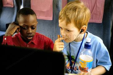 Afrikanischer und Deutscher Junge beim Computerspiel im Bahnabteil
