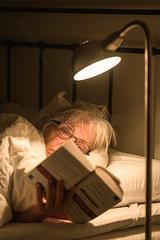 Aeltere Frau liest ein Buch im Bett