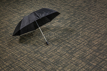 Offener Regenschirm auf einem Teppich