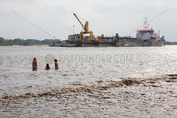Kinder in der Elbe mit grossem Schiff im Hintergrund