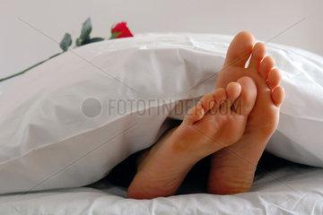 Ein einsames Paar Fuesse guckt unter der Bettdecke hervor