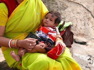Glaeubige Hindu haelt ihr Kind im Arm