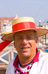 Venice Venezia Italy gondola driver with red straw hat for tourists on Grand Canal