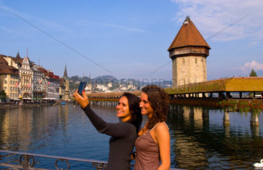 Local girls take photo at famous Kapelbrucke Bridge called Chapel Bridge at lake in Lucerne Switzerland