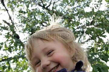 kleiner Junge  3 Jahre alt  schaut ins Objektiv der Kamera und lacht (model released)