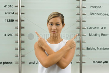 Woman in front of building directory  pointing over shoulders with fingers  looking at camera