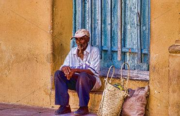 Old man with cigar in doorway of building in old village of Trinidad Cuba