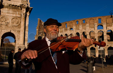 Local man playing violin at famous Colosseum in Rome Italy Landmark Monument in Europe