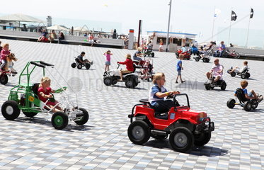 Belgische Nordseek__ste. Kinder in Gokarts auf der Strandpromenade
