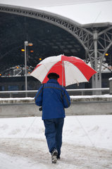 Neuschnee: Spaziergaenger mit Regenschirm am Koelner Hauptbahnhof