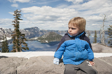 Little boy sitting at Crater Lake National Park in Oregon  USA