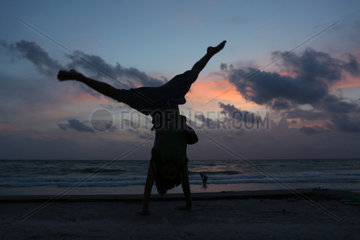 Pass A Grille  Vereinigte Staaten von Amerika  Silhouette  Junge macht einen Handstand bei Daemmerung am Strand