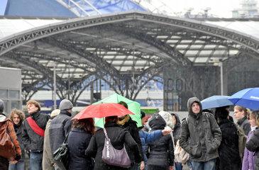 Menschen im Regen vor dem Koelner Hauptbahnhof
