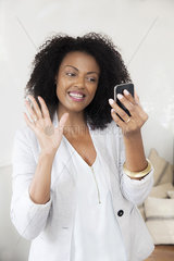 Woman waving at smartphone while doing video chat
