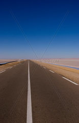 Remote isolated road Great Dry Salt Lake Chott el Jerid in Sahara Desert sand near Douz in Tunisia Africa